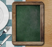 Menu blackboard lying on table with plate, knife and fork — Fotografia Stock