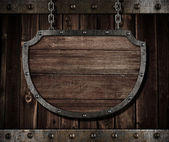 Aged medieval shield signboard hanging on chains — Stock Photo