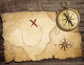 Aged brass antique nautical compass on table with old treasure m — Foto de Stock