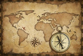 Aged brass antique nautical compass and old map with track on it — Stok fotoğraf