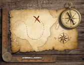 Aged brass antique nautical compass on table with old treasure m — Foto Stock
