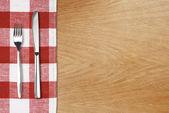 Garfo e tableknife na toalha de mesa de algodão vermelho. tampo de madeira — Foto Stock