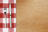 Fork and tableknife on red gingham tablecloth. Wooden table top — Stock Photo