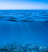 Still calm sea water surface with clear sky and underwater worl — Foto de Stock
