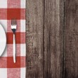 White plate and fork on old wooden table with red checked tablec — Stock Photo #19655105