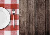 White plate and fork on old wooden table with red checked tablec — Stockfoto