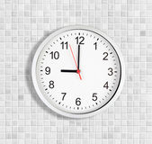 Simple clock or watch on white tile wall displaying nine o'clock — 图库照片
