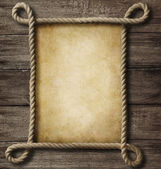 Aged paper with rope frame on old wood background — Stock Photo
