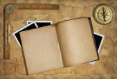 Open diary over old treasure map with compass — Stock Photo