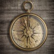 Old brass compass on wood table top view — Stock Photo #23363804