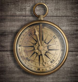 Old brass compass on wood table top view — Stock Photo