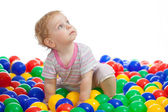 Cute kid or child playing colorful balls looking up — Stock Photo