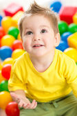 Cute kid or child playing colorful balls top view — Stock Photo