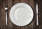 White plate, knife and fork on old wooden table — Stock Photo