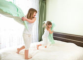 Little girls fighting using pillows in bedroom — Foto de Stock