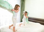 Niñas luchando utilizando almohadas en dormitorio — Foto de Stock