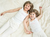 Happy little sisters lying on back top view — Stock Photo