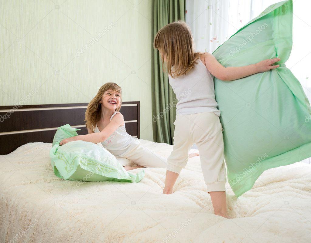 Due ragazze che giocano con cuscini in camera da letto - A letto con due donne ...