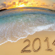 New year 2014 digits on ocean beach sand — Stock Photo #25284893