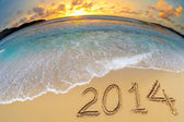 New year 2014 digits on ocean beach sand — Stock Photo