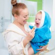 Happy mother and child teeth brushing and tongue cleaning perfor — Stock Photo
