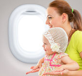 Happy mother and child sitting together in airplane cabin near w — Stock Photo