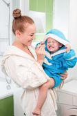 Gelukkig moeder en kind tanden borstelen samen in badkamer — Stockfoto