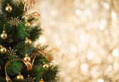Gold Christmas background of defocused lights with decorated tre — Stock Photo