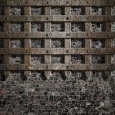 Středověké staré kovovou mřížkou na kamenné zdi — Stock fotografie