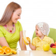 Mother feeding little girl with healthy food sitting at table is — Stock Photo #27709411