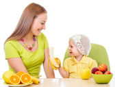Mother feeding little girl with healthy food sitting at table is — Stock Photo