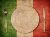 Plate, fork and knife on grunge italian flag — Stock Photo