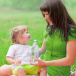 Mother and daughter have picnic drinking water from bottle — Stock Photo #28031269