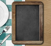 Menu blackboard lying on table — Stock Photo