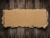 Torn cardboard on wood background — Stock Photo