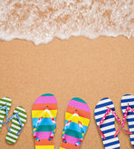 Family's flip flop pairs on sea surf with copy space for your te — Stock Photo