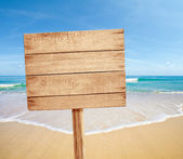 Wood road sign on sea beach — Stock Photo