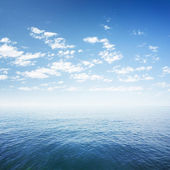 Blue sky over sea or ocean water surface — Stock Photo