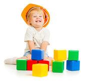 Chlapeček v přilbu s barevnými stavební bloky — Stock fotografie