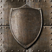 Old metal shield over armour background with rivets — Stock Photo