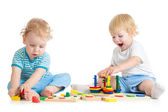 Two kids playing wooden toys together sitting — Stock Photo