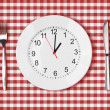Stock Photo: Knife, white plate with clock face and fork on red picnic table