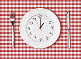 Knife, white plate with clock face and fork on red picnic table — Stock Photo