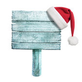 Frozen wooden sign with red Santa's hat — Stock Photo