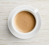 Coffee cup with foam on table top view — Stock Photo