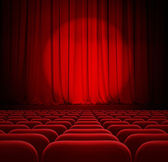 Cinema red curtains with spotlight and seats — Stock Photo