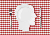 Head dish or plate on red picnic tablecloth with knife and fork — Stock Photo