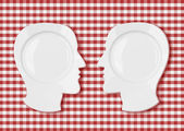 Two head plates face to face on red picnic tablecloth — Stock Photo