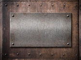 Old metallic plate over rust metal background — Stock Photo