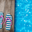 Stock Photo: Flip flop sandals on old wooden boards near swimming pool